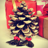 Christmas gifts. Picture of a dry pine cone and some christmas gifts wrapped with wrapping paper of different colors, with a retro effect stock image