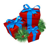 Christmas gifts with pine holly. Showing red presents and blue silk ribbon with green holiday festive winter decoration element as a celebration of giving and Royalty Free Stock Image