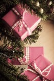 Christmas Gifts in Pink Wrapping. Pink Christmas gift boxes in branches and around base of decorated tree, wrapped in gingham ribbon and tied with bows.  Shot Stock Photography