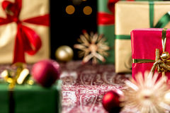 Christmas Gifts Placed on a Festive Cloth. Tightly-framed shot of plain presents in gold and green. Blurred shapes of baubles and stars outside the shallow depth Royalty Free Stock Images