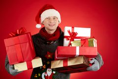 Christmas gifts. Portrait of happy man in Santa cap holding giftboxes and smiling at camera Royalty Free Stock Photography