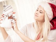 Woman in Santa hat holding gift, snowman decoration. Christmas gifts and presents concept. Blonde woman in Santa Claus hat sitting on couch, holding gift Stock Images