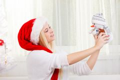 Woman in Santa hat holding gift, snowman decoration. Christmas gifts and presents concept. Blonde woman in Santa Claus hat sitting on couch, holding gift Royalty Free Stock Photography