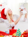 Woman in Santa hat holding gift, snowman decoration. Christmas gifts and presents concept. Blonde woman in Santa Claus hat sitting on couch, holding gift Stock Photos