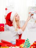 Woman in Santa hat holding gift, snowman decoration. Christmas gifts and presents concept. Blonde woman in Santa Claus hat sitting on couch, holding gift Stock Photography