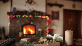 Gifts, presents and packaging materials: wrapping paper, fir tree branches, cones and ribbons on table. Fireplace. Christmas gifts, presents and packaging stock video