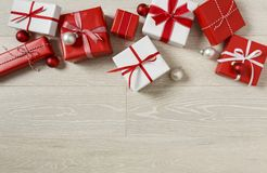 Christmas gifts presents on rustic wood background. Simple, red and white gift boxes festive holiday border.