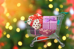 Christmas gifts and presents in shopping trolley cart with blurred lights background. Stock Photo