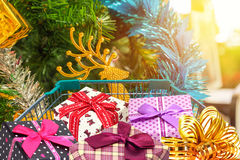Christmas gifts and presents in shopping trolley cart with christmas tree decorations Royalty Free Stock Photo