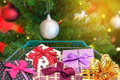 Christmas gifts and presents in shopping trolley cart with christmas tree decorations Stock Image
