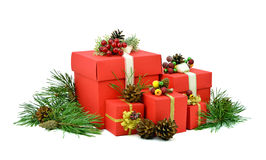 Christmas gifts in red boxes. Pine branches with cones. Isolation. Big pile of Christmas gifts boxes and red pine branch with cones. Isolation on a white stock photos