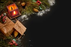 Christmas gifts and red candlestick near green spruce branch on a black background. Christmas background. Top view. Royalty Free Stock Photos