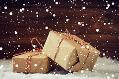 Christmas gifts with red ribbon in snowing. Christmas gift boxes wrapped in brown paper with red ribbon on wooden background in snowing. Shallow focus Stock Photos