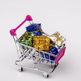 Christmas gifts in shopping trolley, isolated on white Stock Image