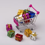 Christmas gifts in shopping trolley, isolated on white Royalty Free Stock Images