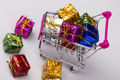 Christmas gifts in shopping trolley, isolated on white Royalty Free Stock Photo