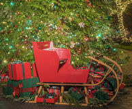 Christmas gifts and sled under the tree Royalty Free Stock Images