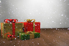 Christmas gifts with snow. Beautiful colorful gifts with shiny wrapping paper in the snow flurry Royalty Free Stock Photos
