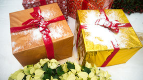 Christmas gifts on snow. Large Christmas gifts on snow with yellow poinsettias. This is a typical Christmas decorations setting. Photo taken on November 22nd Stock Images