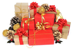 Christmas gifts. Some christmas gifts wrapped with wrapping paper of different colors and ribbon bows, and some christmas ornaments on a white background royalty free stock photo