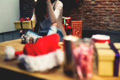 Christmas gifts in a table with woman sitting on the floor in the background. Royalty Free Stock Image