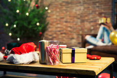 Christmas gifts on a table with woman sitting on a sofa in the background. Stock Images