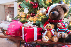 Christmas gifts and teddy bears under decorated Christmas tree. Decorated Christmas tree  with red present box and teddy bear near fireplace Royalty Free Stock Photography