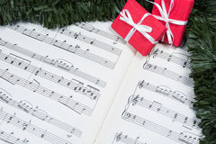 Christmas gifts with tinsel on music notes Stock Photos