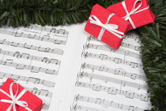 Christmas gifts with tinsel on music notes Royalty Free Stock Photo