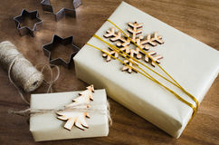 Christmas Gifts. Top View of Festive Boxes Decorated with Wooden Snowflake, Christmas Tree and Jute on Wooden Table. Royalty Free Stock Photo