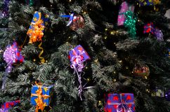 Christmas gifts in tree decoration. Colorfully wrapped gifts hanging in a lighted Christmas tree Royalty Free Stock Image
