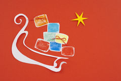 Christmas gifts and tree on a sled on red paper background Stock Photos