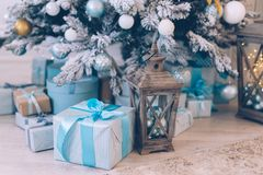 Christmas gifts under the Christmas tree. Christmas presents in boxes lie near the decorated Christmas tree Stock Photos