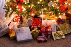 Christmas Gifts Under the Tree. Colorful Christmas packages under a Christmas Tree Stock Photo