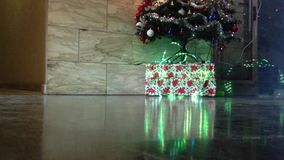 Christmas gifts under the tree. Lights background switched on stock video footage