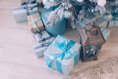 Christmas gifts under the Christmas tree. Christmas presents in boxes lie near the decorated Christmas tree Royalty Free Stock Photography