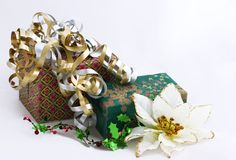 Christmas gifts w poinsettia. Gifts nicely decorated on white background Stock Photos
