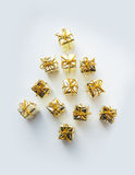 Christmas gifts wrapped in gold on white bacground Stock Photo
