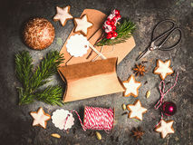 Christmas gifts wrapping . Flat lay with Cardboard boxes, cookies , fir twigs and scissors on dark wooden background Royalty Free Stock Image
