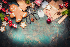 Christmas gifts wrapping with gingerbread man, star cookies, shears and handmade cardboard boxes on vintage background, top view Stock Photography