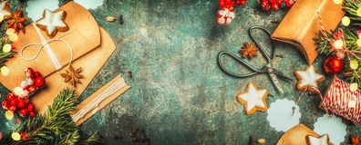 Christmas gifts wrapping with little cardboard boxes , shears, holiday cookies and festive decorations on vintage background, top. View, banner stock photos