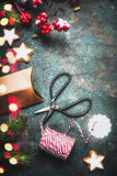 Christmas gifts wrapping with paper boxes and tying them up with red rope, old scissors and red green holiday decorations, top vi Stock Photos