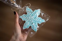 Christmas ginger cookie in the form of a snowflake held in a hand. Blue ginger cookie held in hand  on a brown background Royalty Free Stock Image