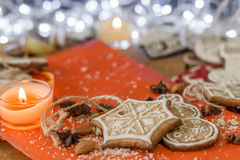 Christmas ginger cookies, candle, almonds and spices on a red and wooden background. Christmas ginger cookies covered with white icing, one orange candle and Royalty Free Stock Photo