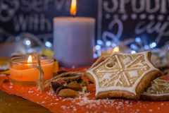 Christmas ginger cookies, candles, almonds and spices on a red paper. Christmas ginger cookies covered with white icing, orange and big blue candles, almonds Stock Image