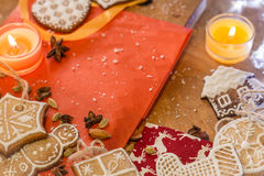 Christmas ginger cookies, candles, almonds and spices on a red paper and wood Stock Photography