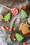 Christmas ginger cookies, cane, lollipop and sweet candy strewn with snow Royalty Free Stock Photos