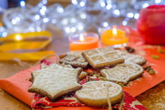Christmas ginger cookies illuminated by white lights and candles. Christmas ginger cookies covered with white icing, almonds and spices on a light brown wooden Royalty Free Stock Photos