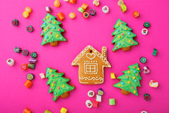 Christmas ginger cookies and mixed multicolored sweet candy. On pink background Stock Photos
