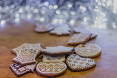 Christmas ginger cookies with white icing. Christmas ginger cookies covered with white icing on a light brown wooden background and illuminated by white lights Royalty Free Stock Photo